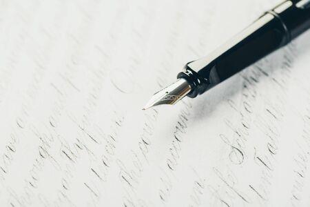 Füllfederhalter auf Papier mit Tintentextnahaufnahme Standard-Bild