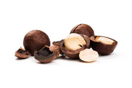 Nueces de macadamia sin cáscara y sin cáscara sobre fondo blanco. Foto de archivo