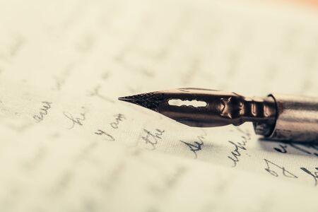Wieczne pióro na starożytnym odręcznym piśmie. Stara historia. Styl retro.