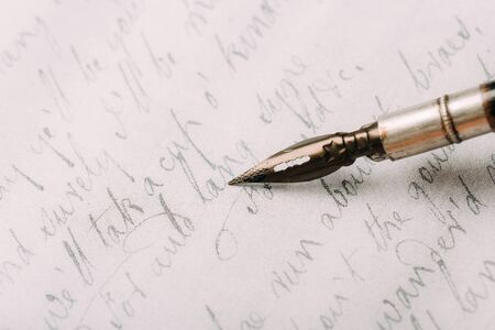 Fountain pen on an ancient handwritten letter. Old story. Retro style.