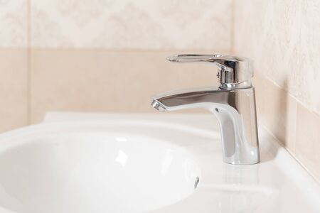 Modern metal faucet and white bathroom sink
