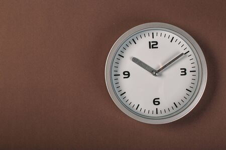 minimalistic white wall clock with light metal on a brown background. time concept.