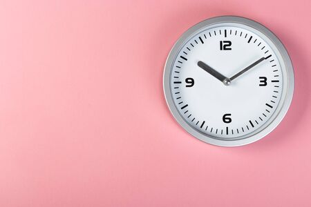minimalistic white wall clock with light metal on a pink background. time concept. Zdjęcie Seryjne