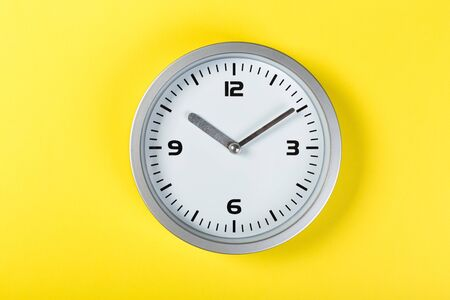 minimalist white wall clock with light metal on a yellow background. time concept.