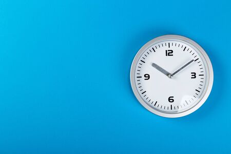 minimalistic white wall clock with light metal on a blue background. time concept.