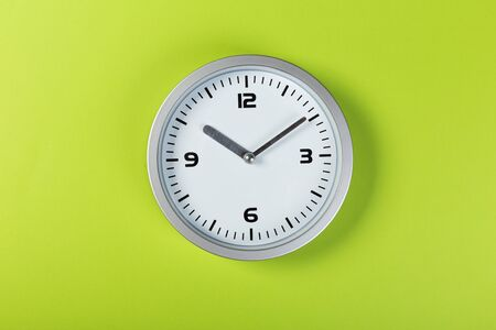 minimalistic white wall clock with light metal on a green background. time concept. Zdjęcie Seryjne