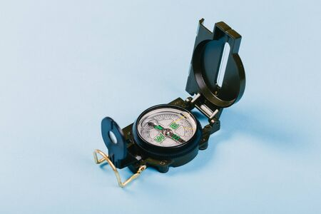 Modern nautical metal tourist compass on a blue background. travel or search concept Imagens