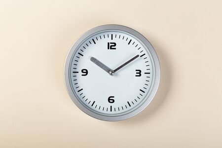 minimalistic white wall clock with light metal on a beige background. time concept.