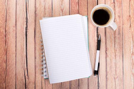 Cahier de papier vide sur fond de table en bois marron. Vue de dessus Concept d'un nouveau lieu de travail de bureaux.