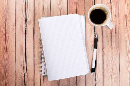 Empty paper notebook on brown wooden table background. Top view Concept of a new workplace of office desks.