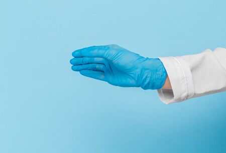 Doctor's hand in a blue medical glove holds an object on a blue background.  mocap, you can insert your product for advertising Stock Photo