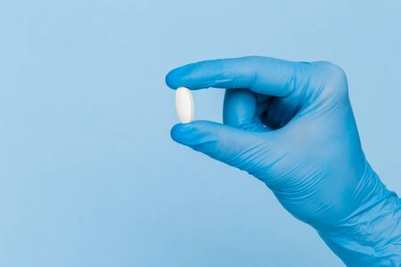 A hand in a blue medical glove holds one pill on a blue background. Treatment