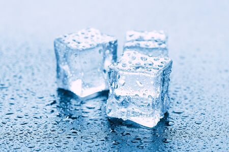 Ice cubes square with drops water clean on blue background.