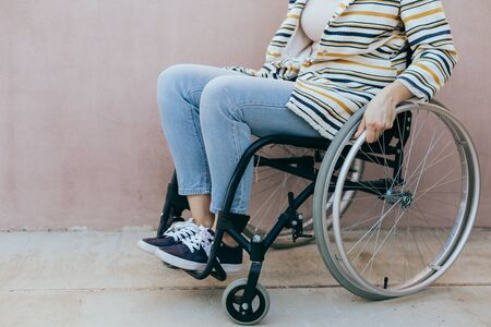 Unrecognizable disabled woman young woman in a wheelchair outdoors in a park. Recovery and healthcare concepts. Stockfoto