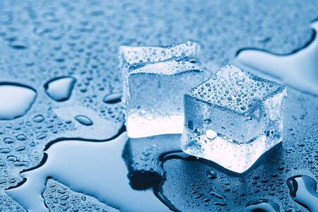 Carré de glaçons avec gouttes d'eau propre sur fond bleu. Banque d'images