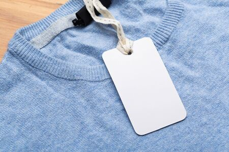 Clothing tag, label blank mockup on a clothes, to place your design. fashion, people and shopping concept - close up price tag of clothing item