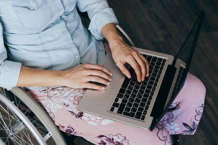 Woman in a wheelchair at home with a laptop on her lap, hand close up Stok Fotoğraf