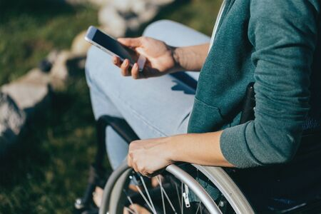 A woman in a wheelchair with a phone in her hand walks on the street, her hand is close up, an unrecognizable