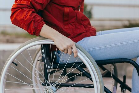 Unrecognizable disabled woman young woman in a wheelchair outdoors in a park. Recovery and healthcare concepts. Stok Fotoğraf