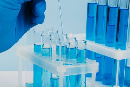 Laboratory glassware with test tubes. scientific laboratory equipment. hands of a scientific researcher in blue gloves