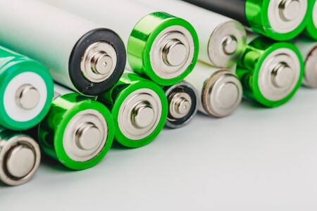 many new and used alkaline batteries type AA on a light background. 版權商用圖片