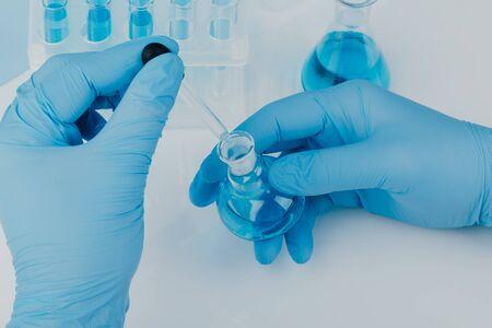 Laboratory glassware with test tubes. scientific laboratory equipment. hands of a scientific researcher in blue gloves Foto de archivo
