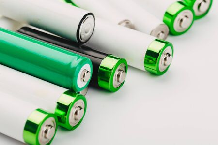 many new and used alkaline batteries type AA on a light background.