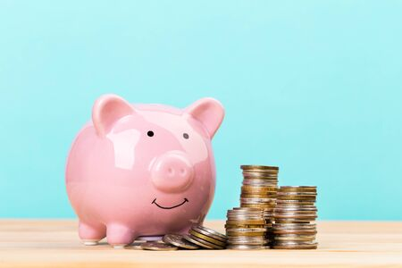 Pink piggy bank on wooden table and blue background. The concept of storage, accumulation. Crisis, inflation, financial collapse.