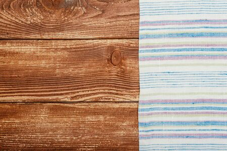 Top view on a dark wooden table with a linen kitchen towel or textile napkin. a tablecloth on a countertop made of old wood. Copy space for text.