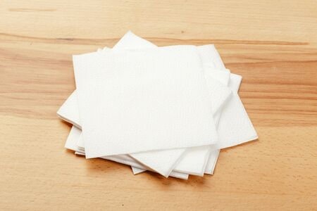 white paper napkin or tissue on the wooden table background.