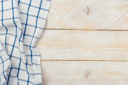 Top view on a white wooden table with a linen kitchen towel or textile napkin. a tablecloth on a light wood countertop. Copy space for text. Stock fotó