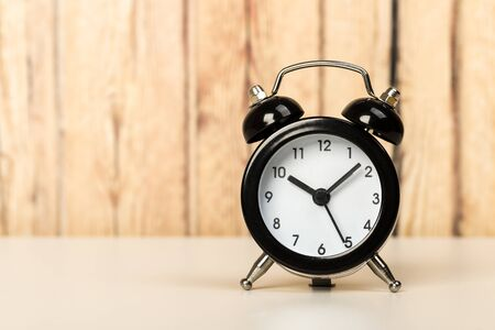 Black retro alarm clock with bells on a wooden table, daily routine concept. ten hours 10 minutes