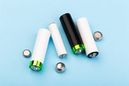 many new and used AA batteries on a blue background.