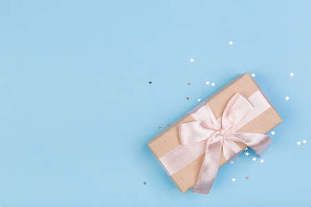 Gift or gift box and stars confetti on a blue table from above. Flat composition for birthday, mothers day or wedding. Stok Fotoğraf