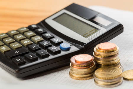 Coin money and banknote bills with a calculator. savings, finance, economics Stock Photo
