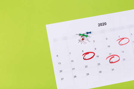Open calendar on the table with green background, planning a business meeting or travel planning concept Фото со стока