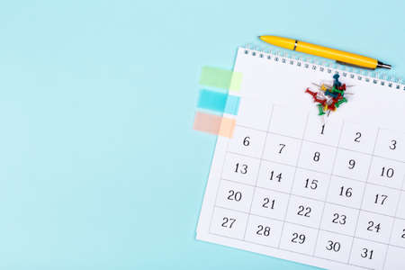 close up top view on white calendar 2020 month schedule to make appointment meeting or manage timetable each day lay on blue background for planning work and life concept Фото со стока
