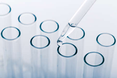 pipette with a drop and scientific laboratory test tubes in a research laboratory. study of a virus or vaccination.