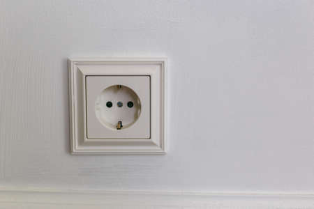 White plastic outlet with grounding on a gray background. Wall with copy space. Minimalism.