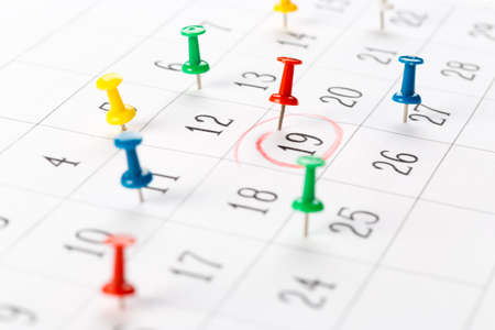 Thumbtack in calendar concept for busy, appointments and meeting reminders Stockfoto