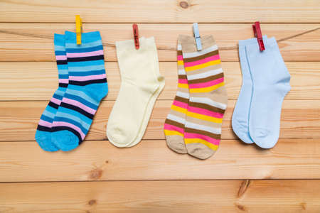 multicolored socks hanging on a clothesline with clothespins on a wooden background