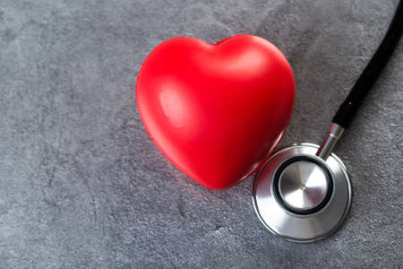 Stethoscope and red heart on a stone table. Cardiology concept