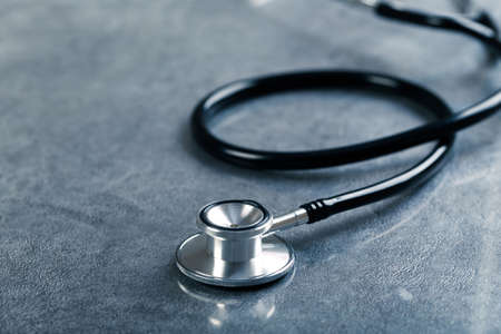 black stethoscope with reflection on glossy background for medical examination of health laboratory