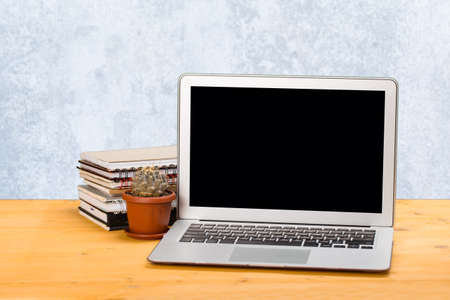 Laptop with blank screen, place for text and notebooks and green cactus on a wooden table.