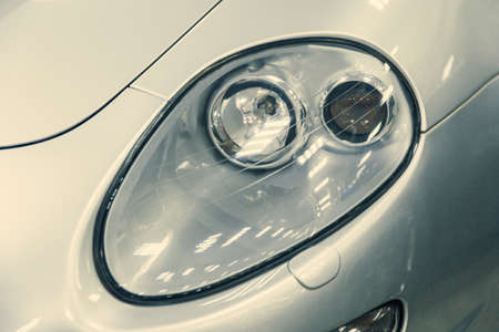close-up of headlight of white retro car. off, car in garage