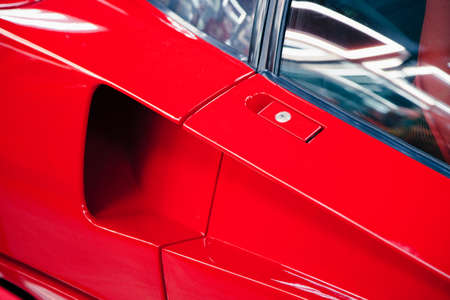 close-up of a door handle with a keyhole in a red sports car