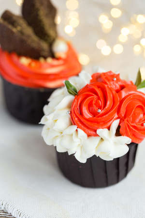 Cupcakes or muffins with chocolate cream and sweets. Cake celebration, delicious dessert, close-up