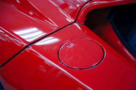 A close up of a petrol cap cover on a modern red car