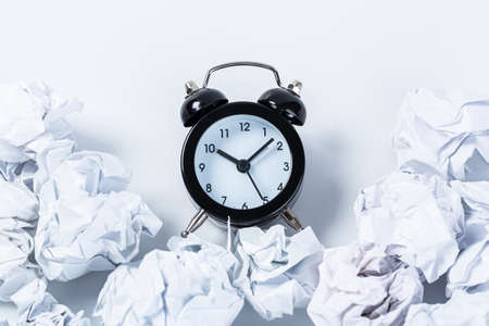 Alarm clock with crumpled paper balls. Timing and thinking idea concept.