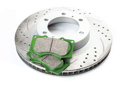 Perforated brake pads next to brake disc on white background isolated object